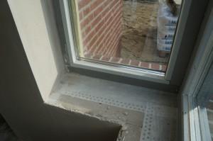 Een met Fentrim 20 luchtdicht afgeplakt kozijn tegen een massief binnenblad, afgestuukt. In dit geval een Ytong paneel, maar dat kan ook beton of kalkzandsteen zijn.